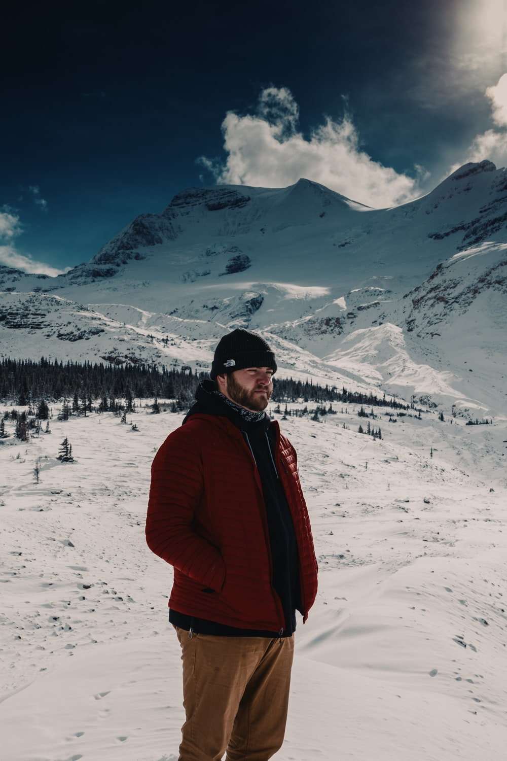 man in red jacket standing on snow covered ground