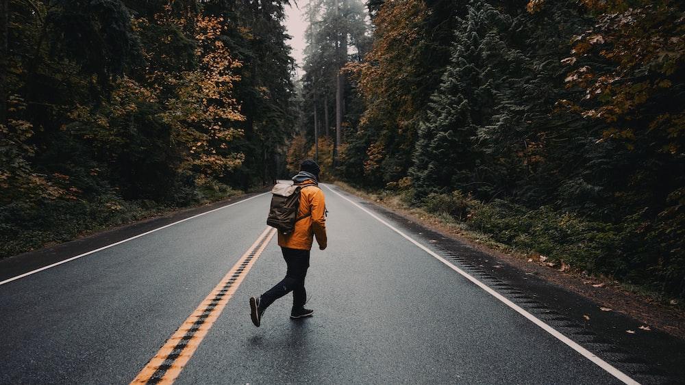 man in brown jacket and black pants walking on the road