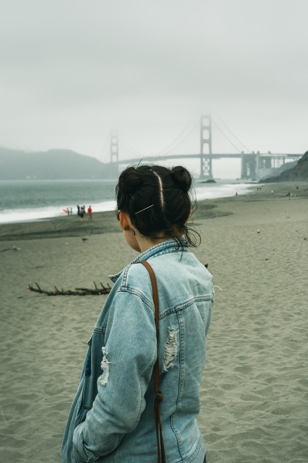 woman in blue denim jacket standing on beach during daytime