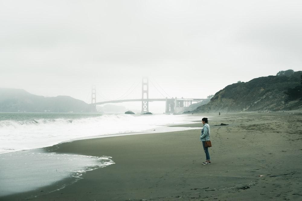 woman in white jacket walking on seashore during daytime