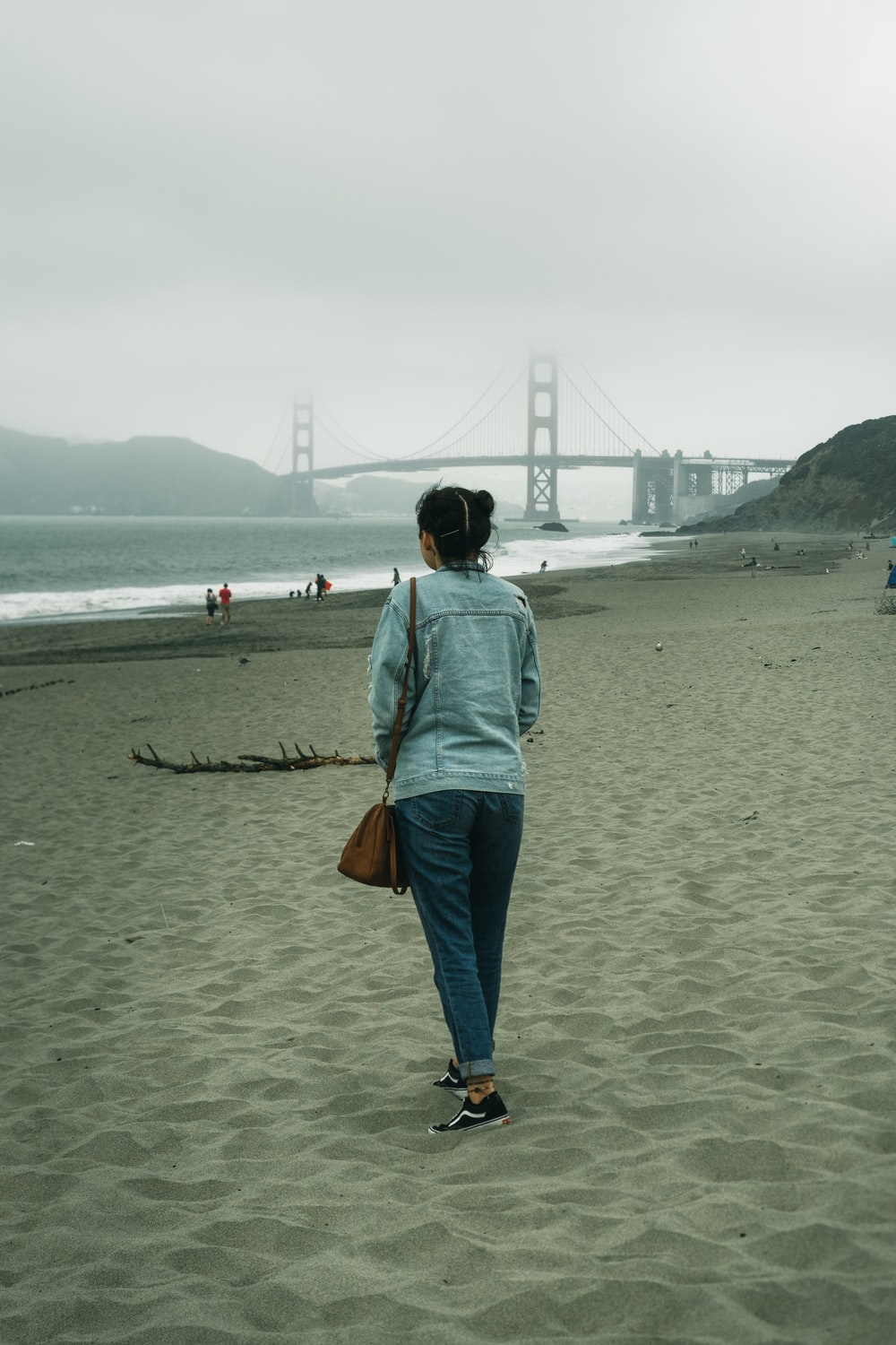 woman in blue hoodie standing on beach during daytime