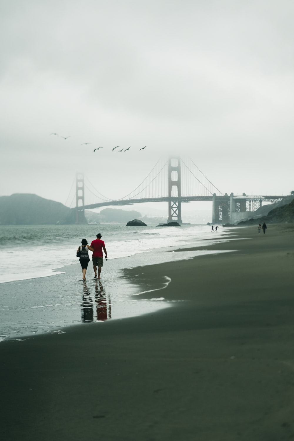 woman in red jacket and black pants walking on beach during daytime