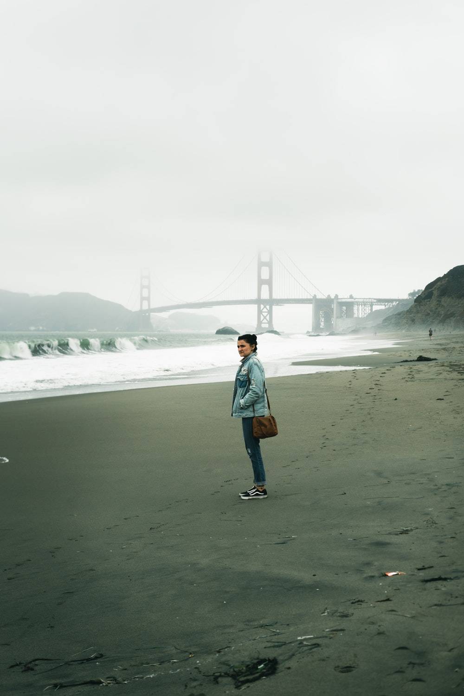 man in white jacket standing on seashore during daytime