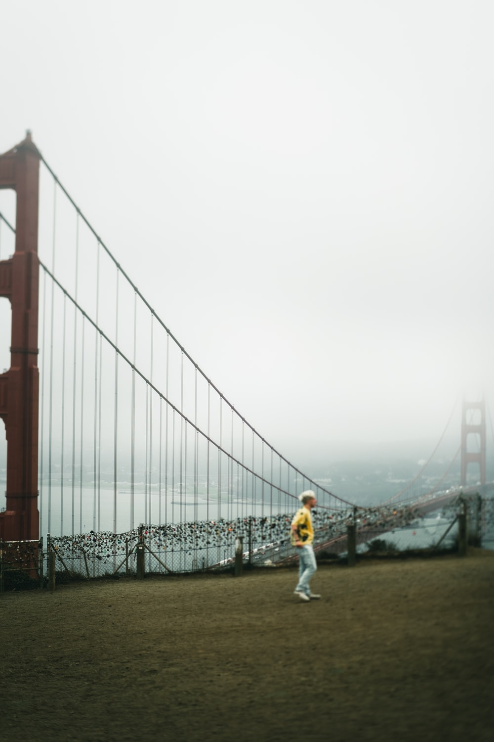 woman in white jacket standing on brown field near bridge during daytime