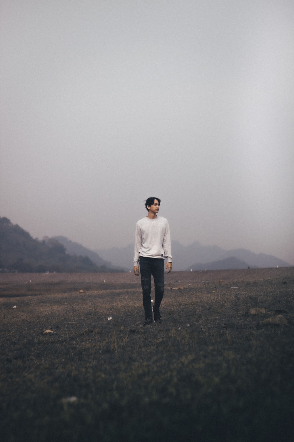 man in white long sleeve shirt standing on green grass field during foggy weather