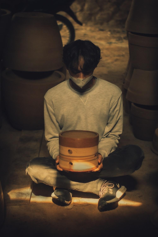 man in gray sweater sitting on floor
