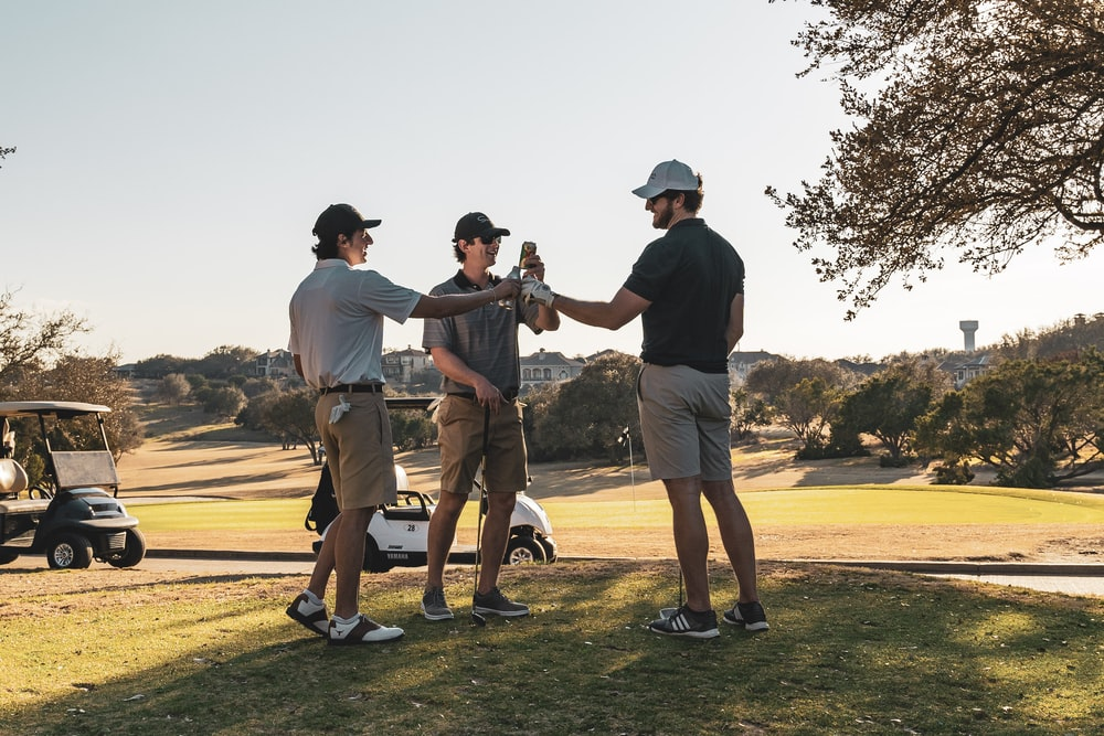 man in black t-shirt and brown shorts playing golf during daytime