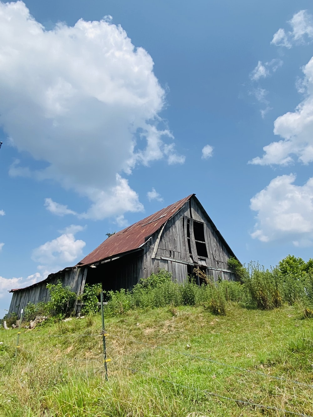 brown wooden barn on green grass field under blue and white sunny cloudy sky