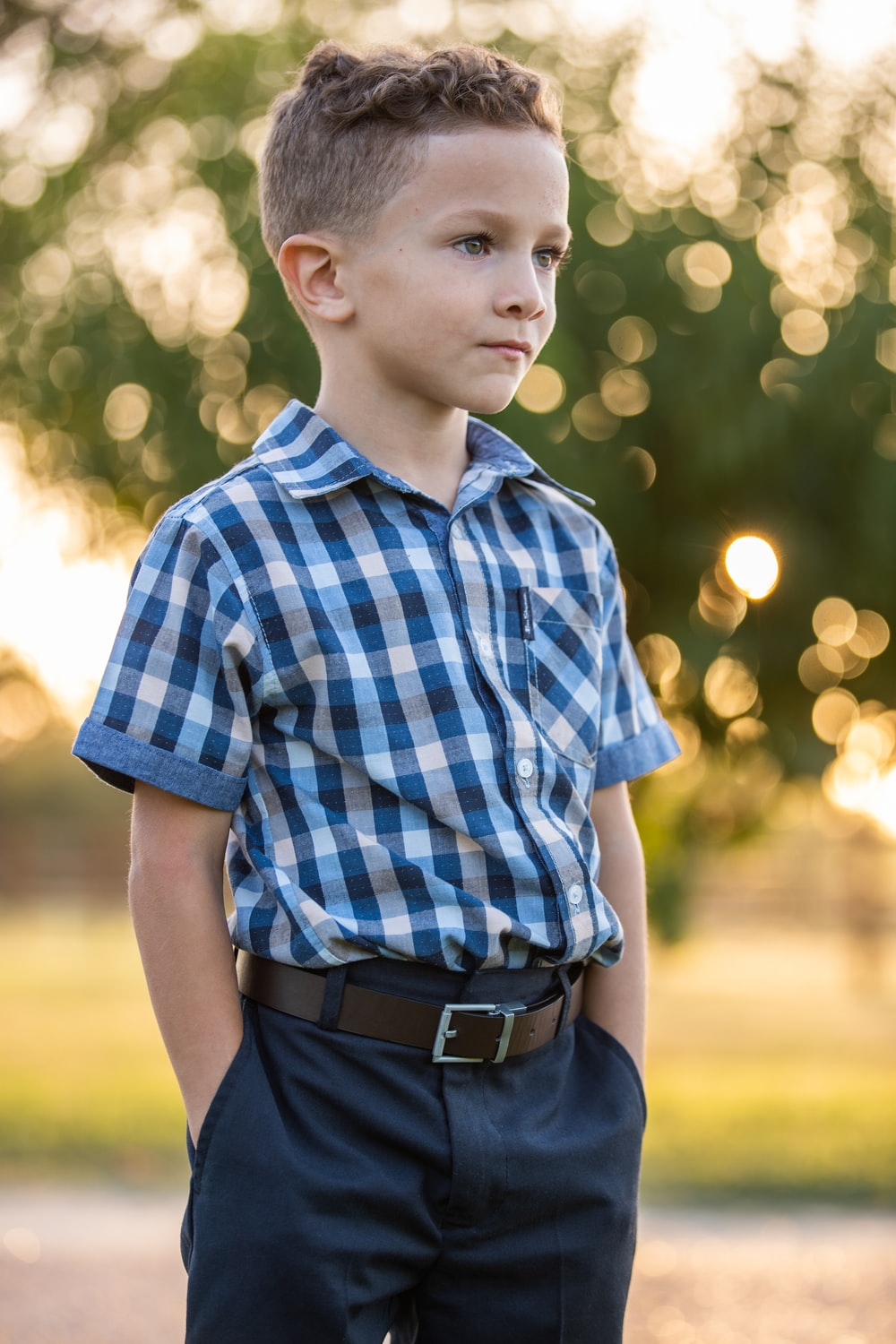boy in blue and white plaid button up shirt and black pants