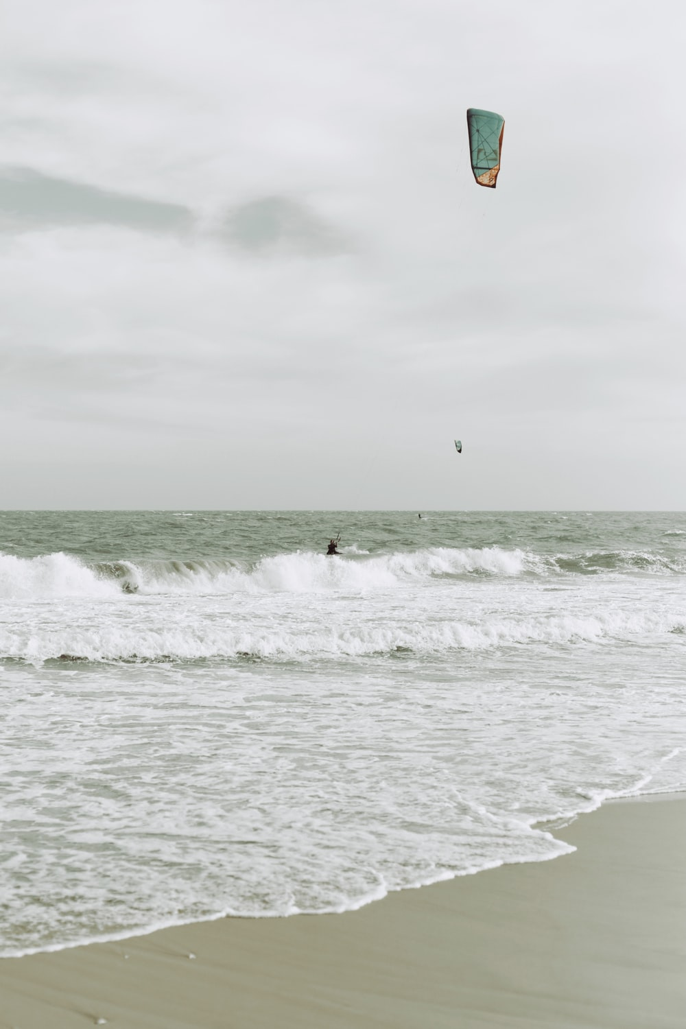 person in red and yellow parachute over sea waves during daytime