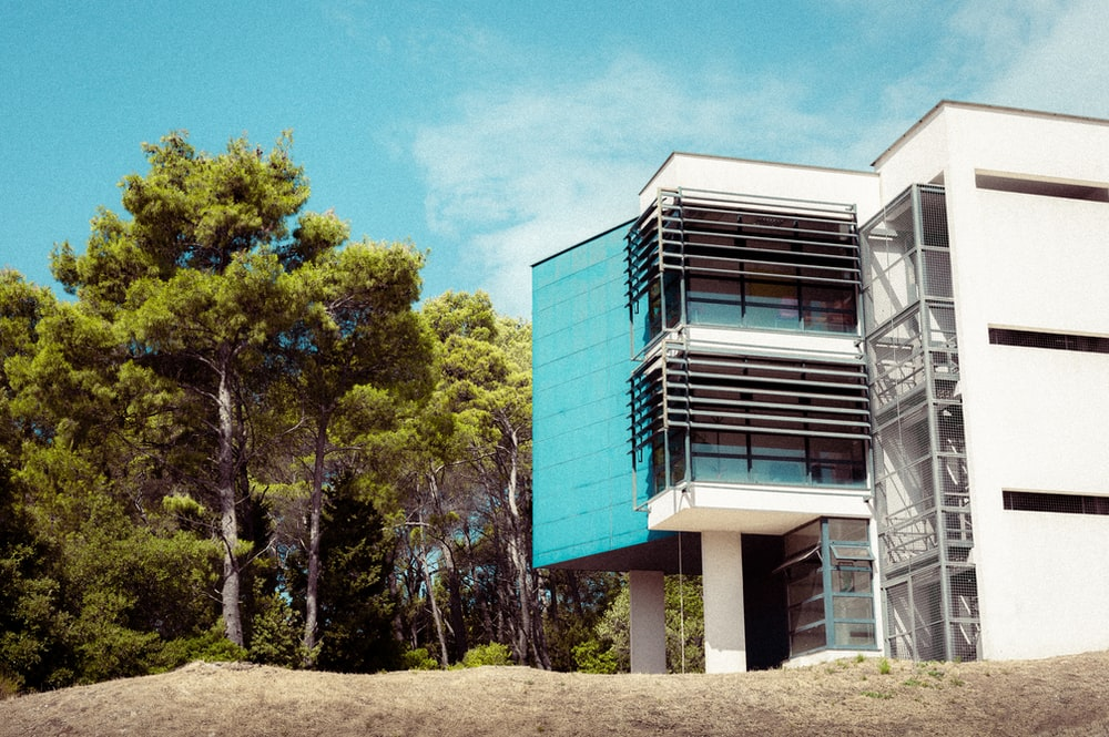 blue and white concrete building near green trees under blue sky during daytime