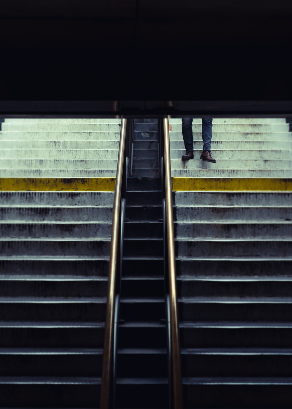 person in black pants walking on gray concrete stairs