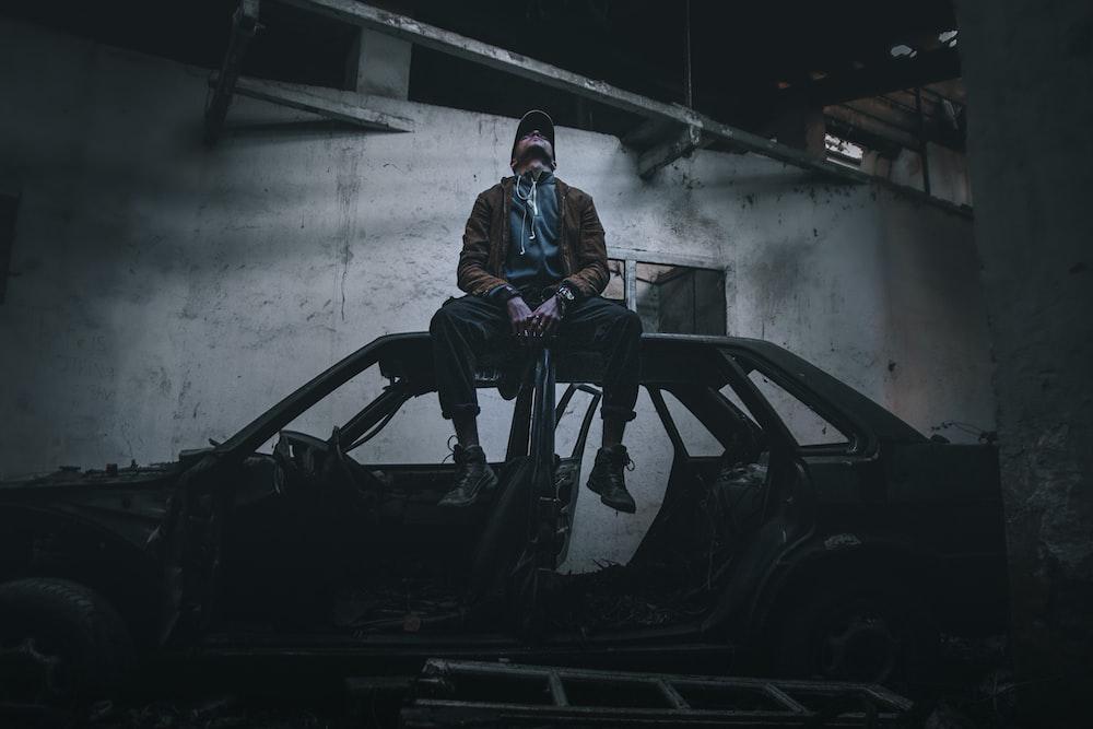 man in blue jacket standing beside black car