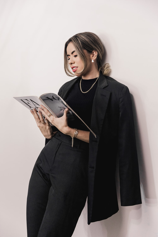 woman in black blazer holding book