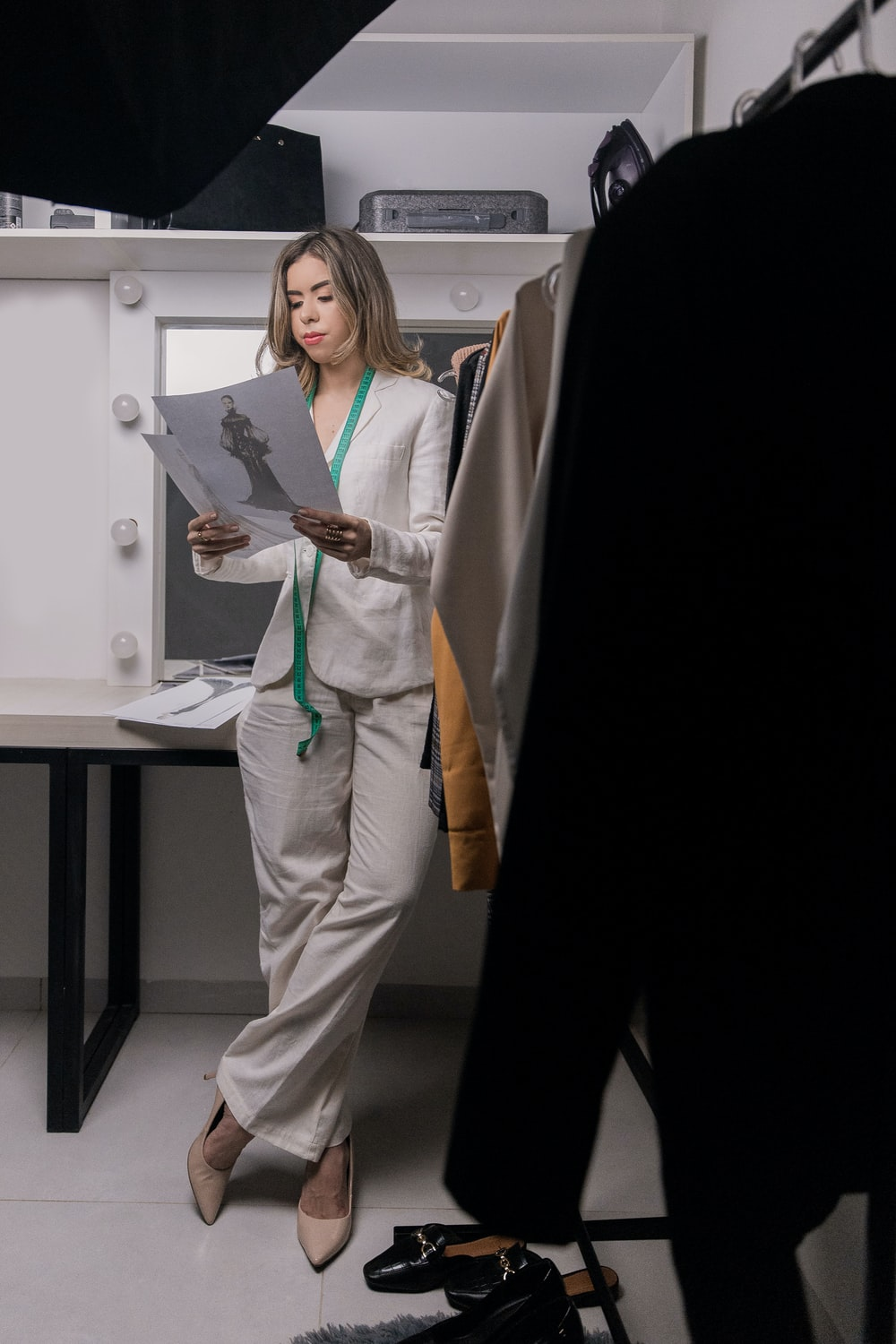 woman in white blazer and white pants standing beside white table