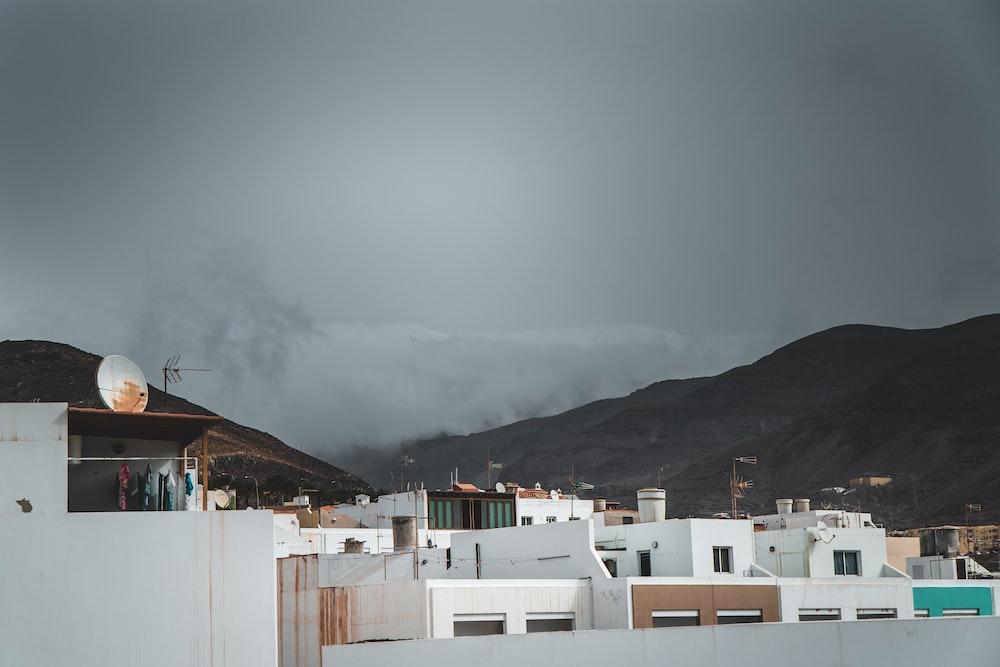 white concrete houses near mountain under gray sky