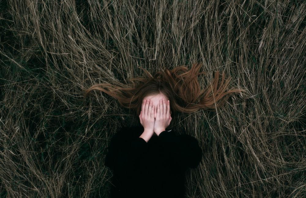 woman in black long sleeve shirt lying on brown grass field