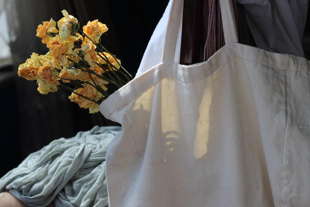 white textile near yellow flowers