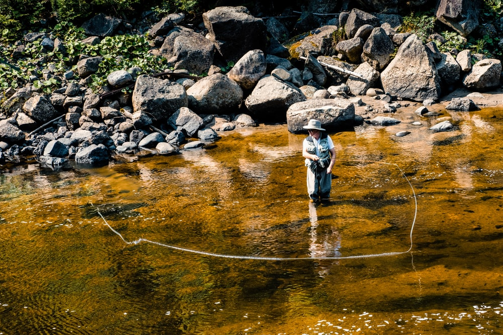 man in black jacket and black pants fishing on river during daytime
