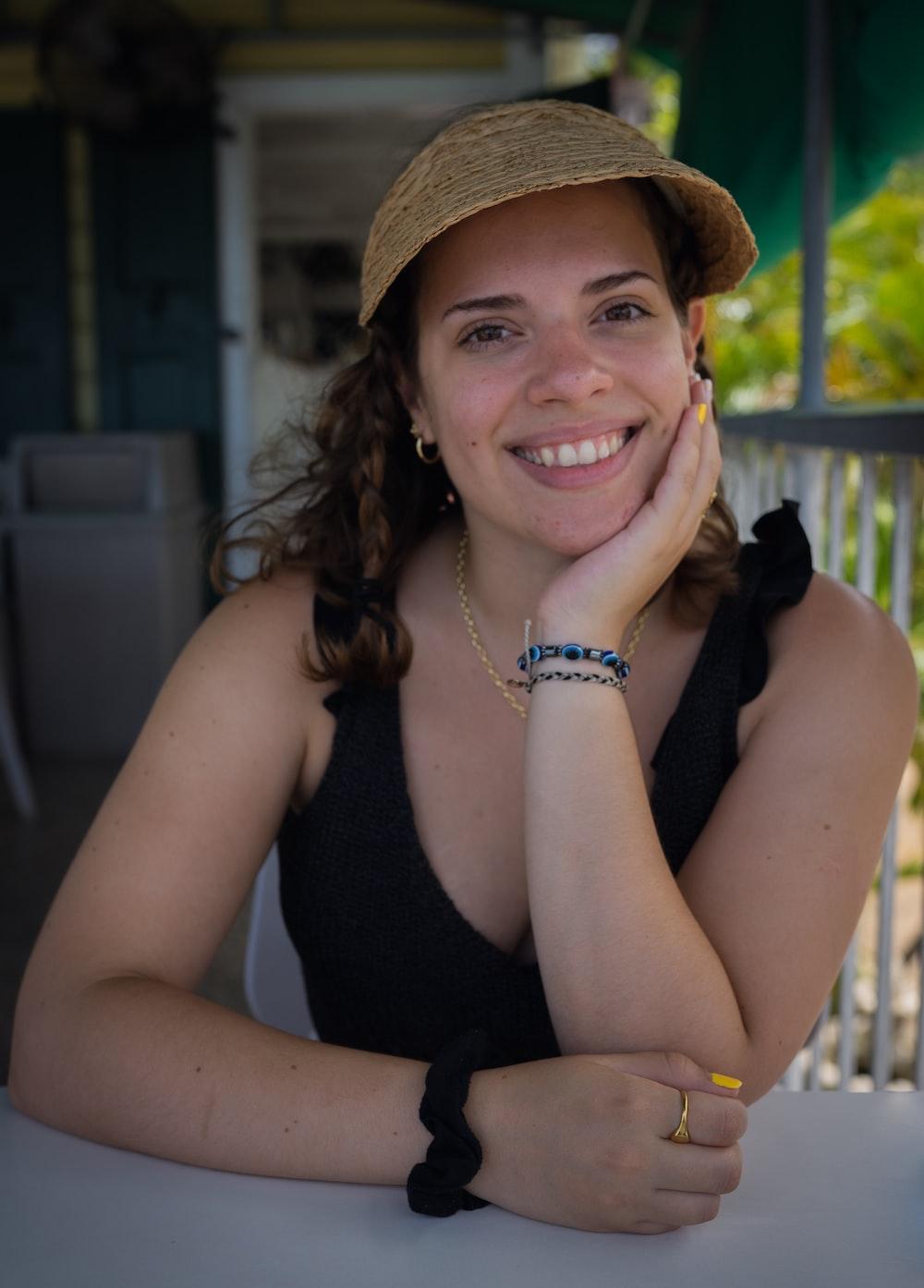 smiling woman in black tank top wearing brown hat