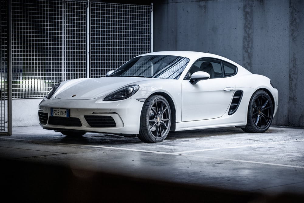 white porsche 911 parked in front of gray building