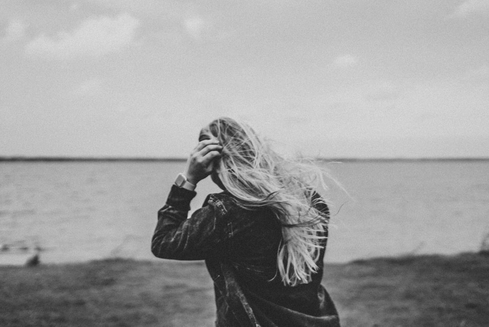 grayscale photo of woman in black jacket standing near body of water