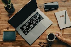 macbook pro beside black iphone 5 on brown wooden table