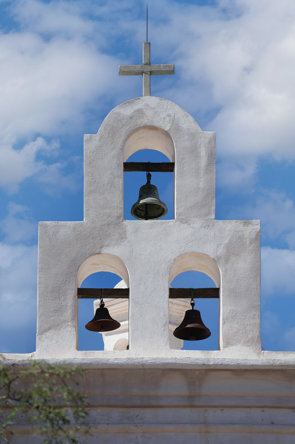 gray concrete bell under blue sky during daytime
