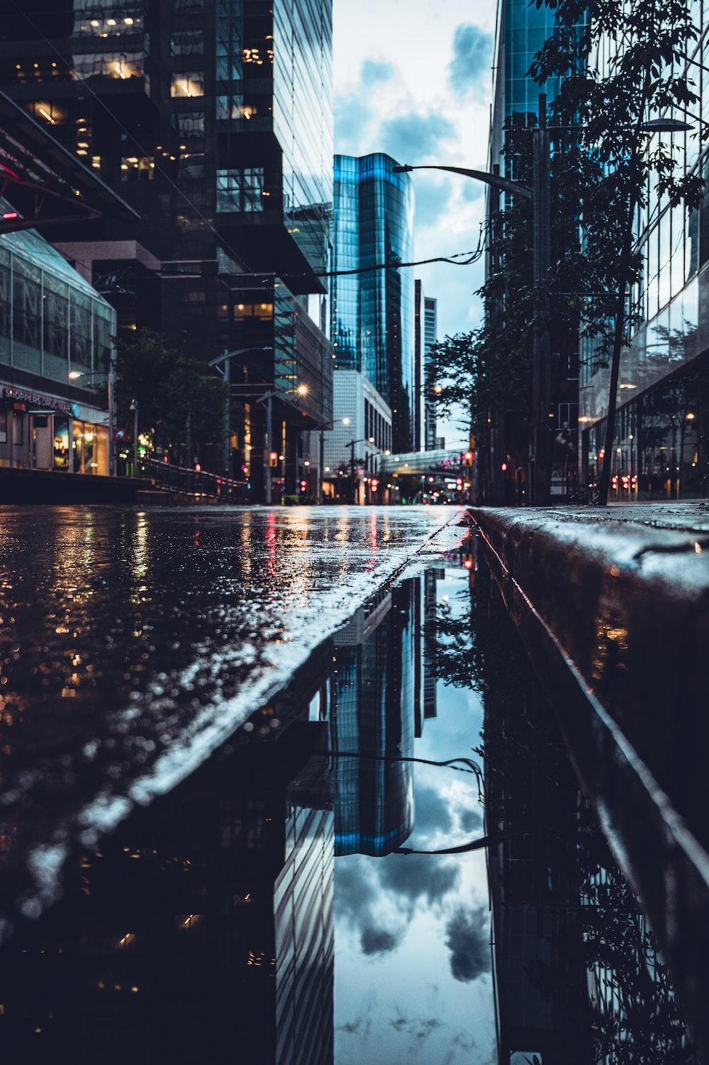 water on road between buildings during daytime