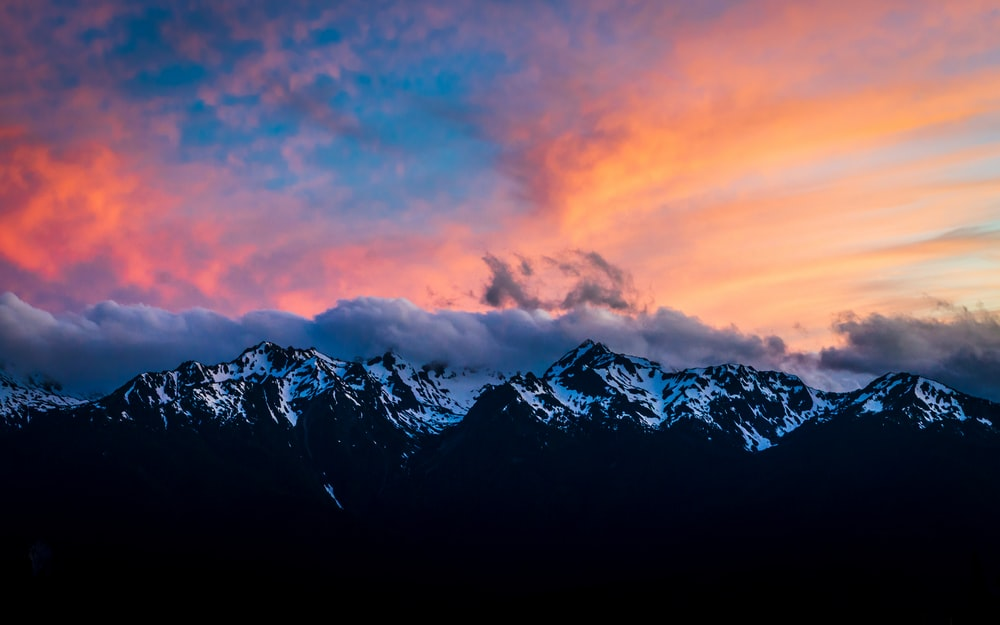 snow covered mountain under orange and blue sky