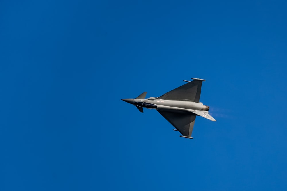 gray jet plane in mid air during daytime