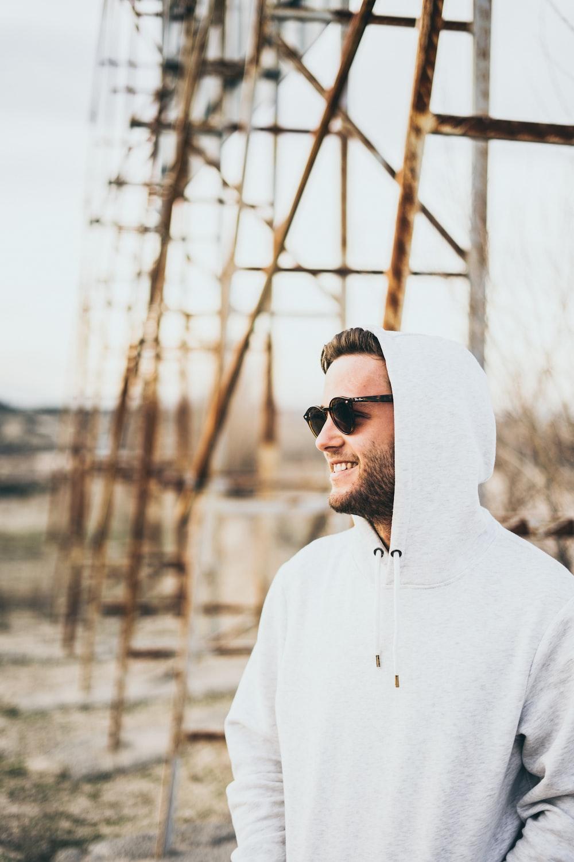 man in white hoodie wearing black sunglasses