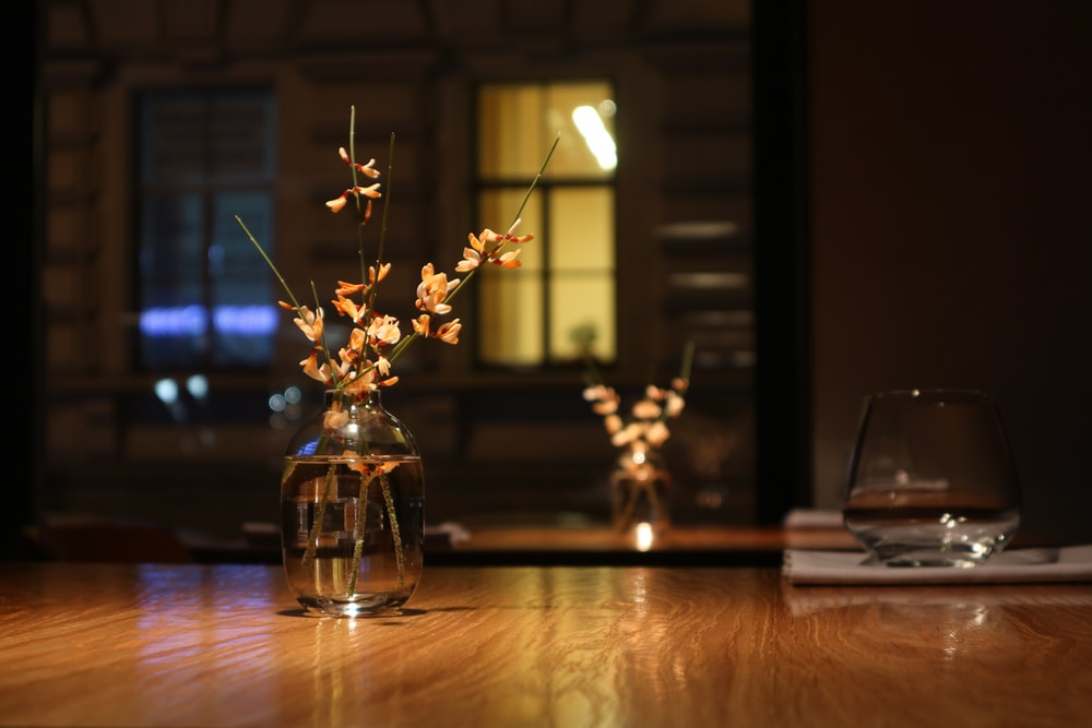 white flowers in clear glass vase on brown wooden table