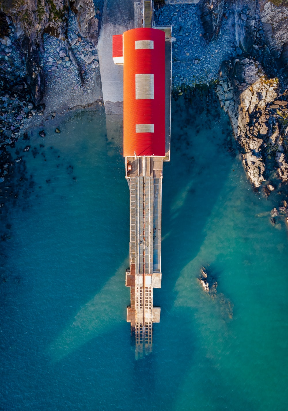 red and white tower near body of water during daytime