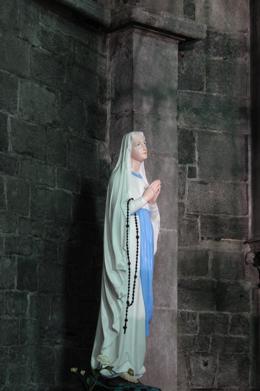 woman in blue hijab standing beside brown brick wall