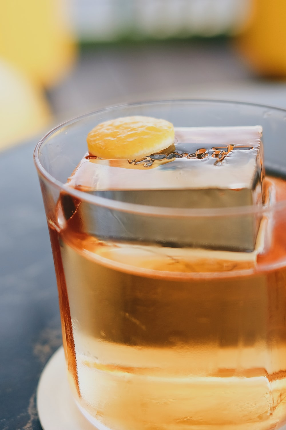 clear drinking glass with brown liquid and sliced lemon
