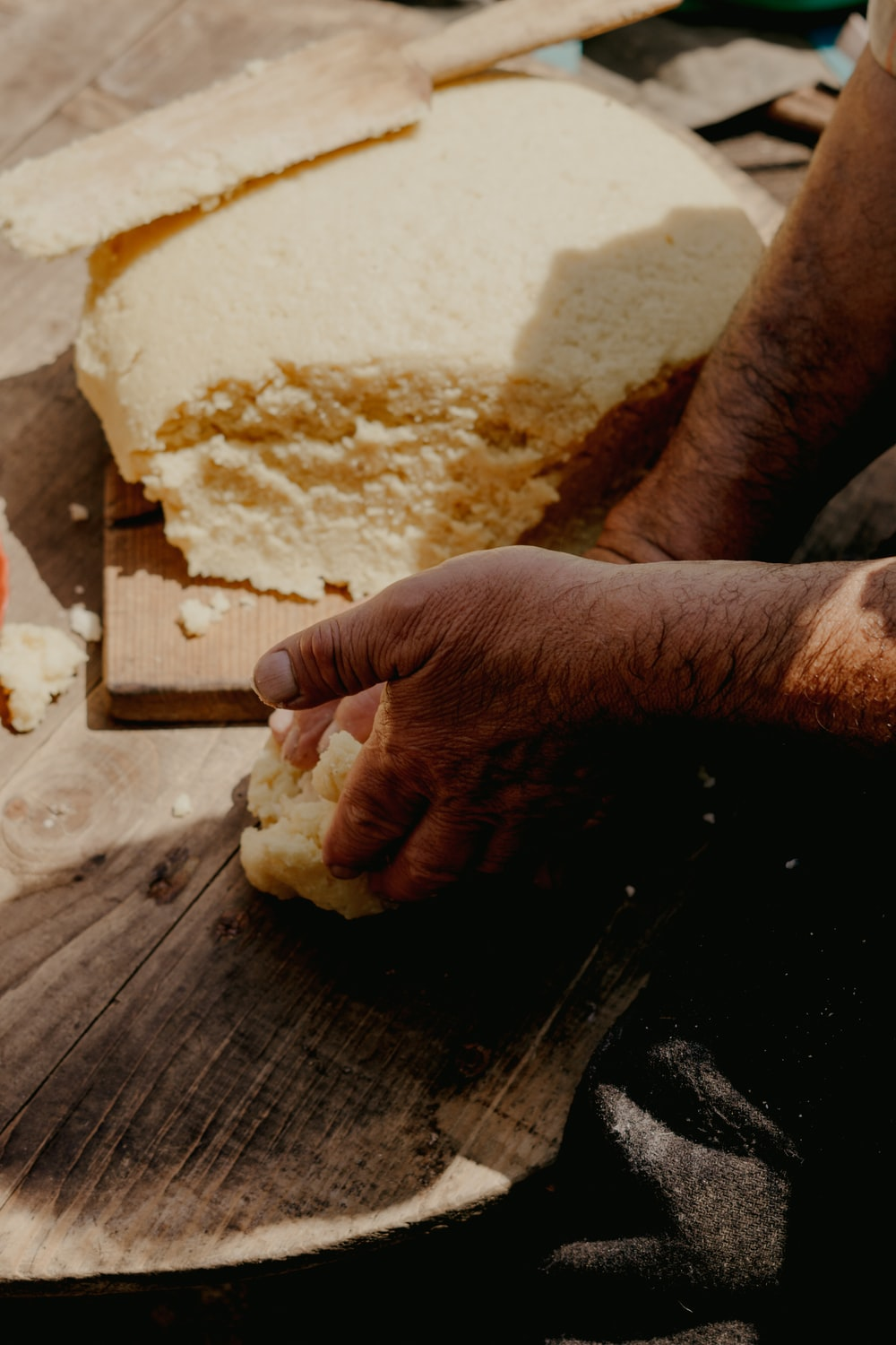 person holding brown wooden rolling pin