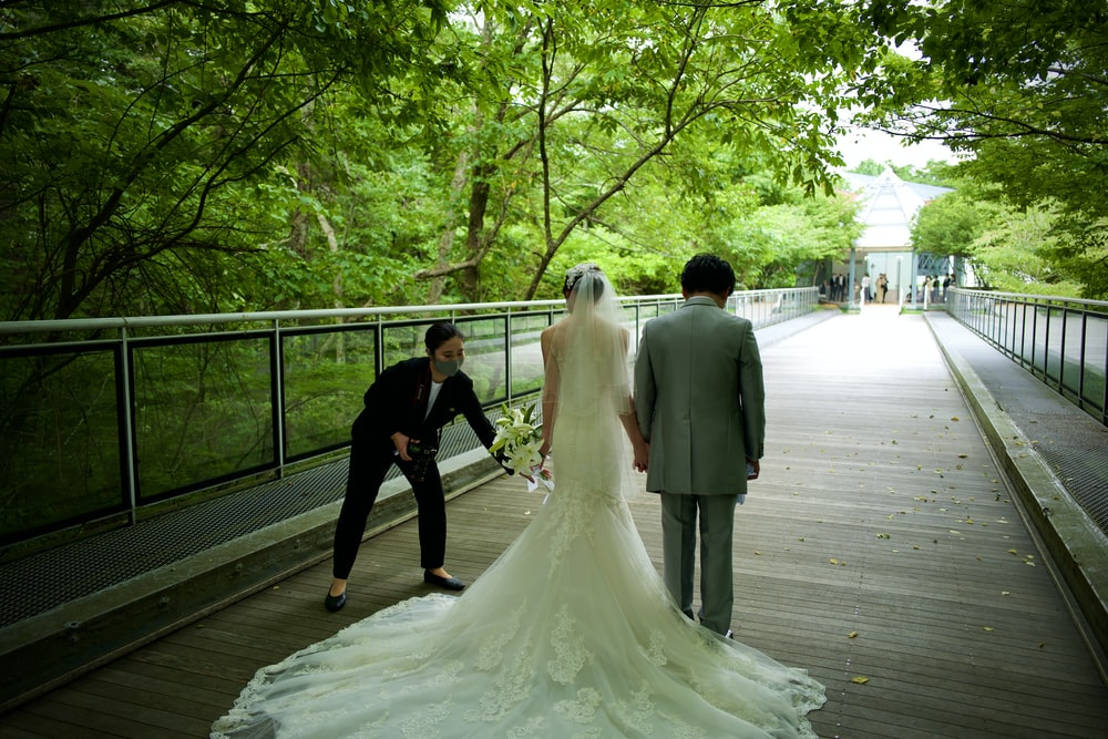 bride and groom walking on wooden bridge