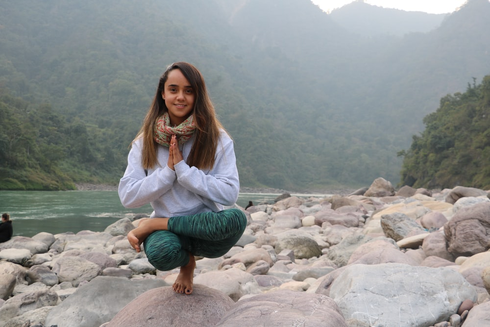 woman in white jacket sitting on rock