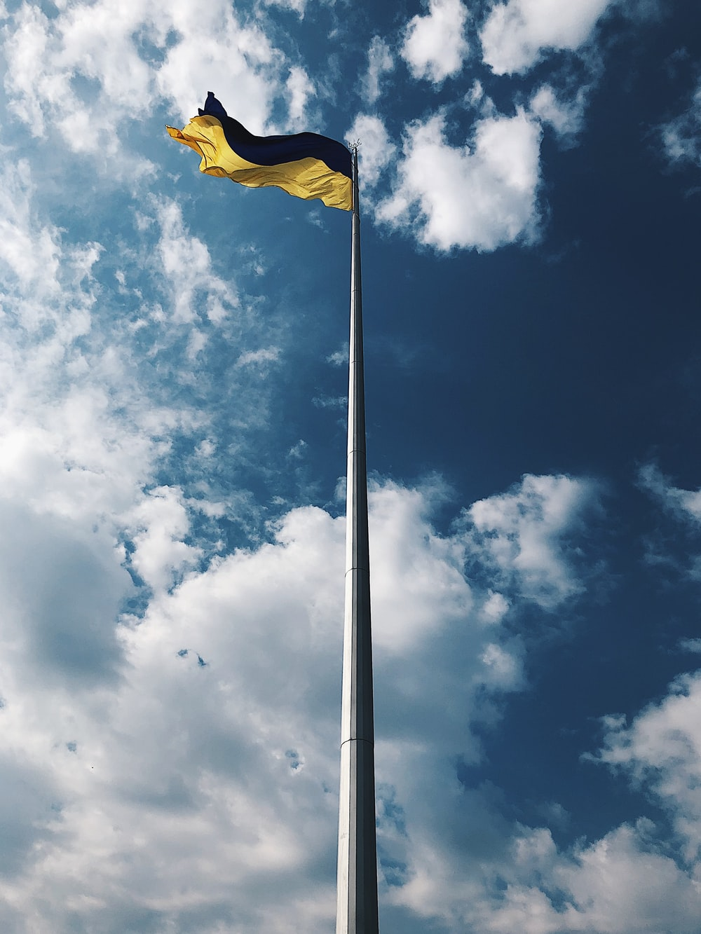 yellow flag under white clouds and blue sky during daytime