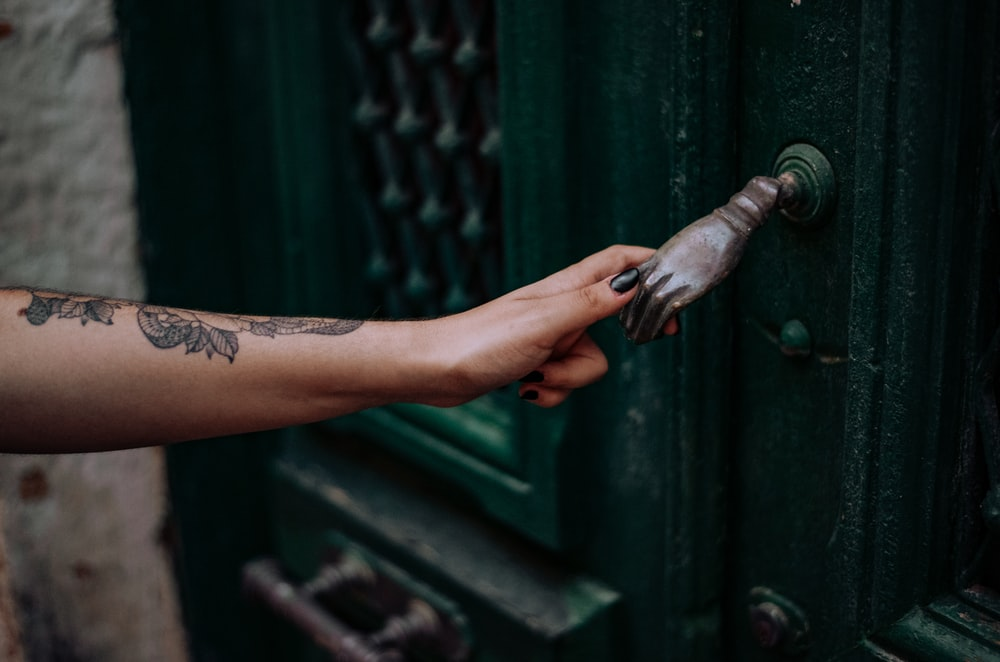 person holding green metal pipe