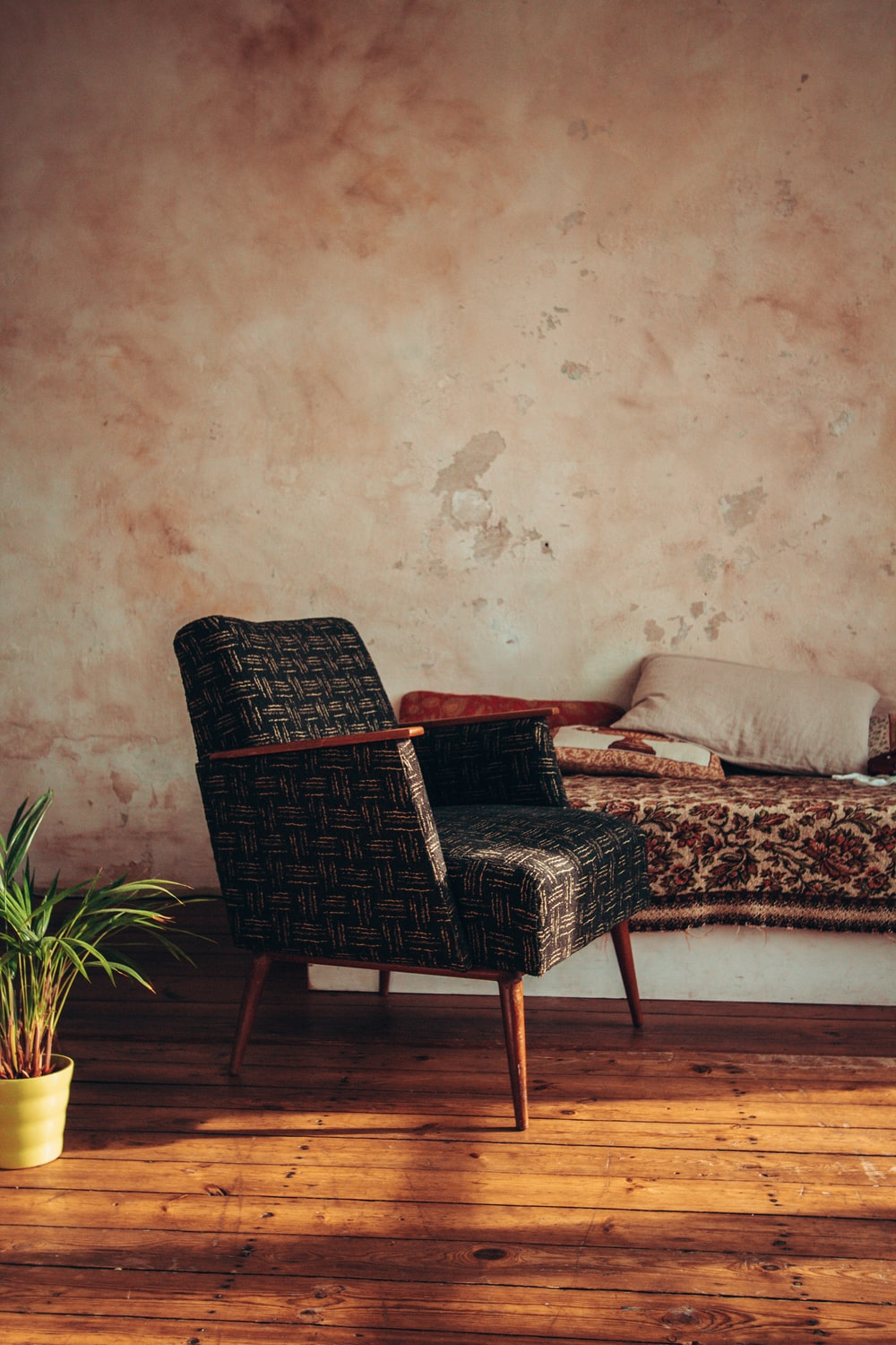 black woven armchair beside white and brown floral couch