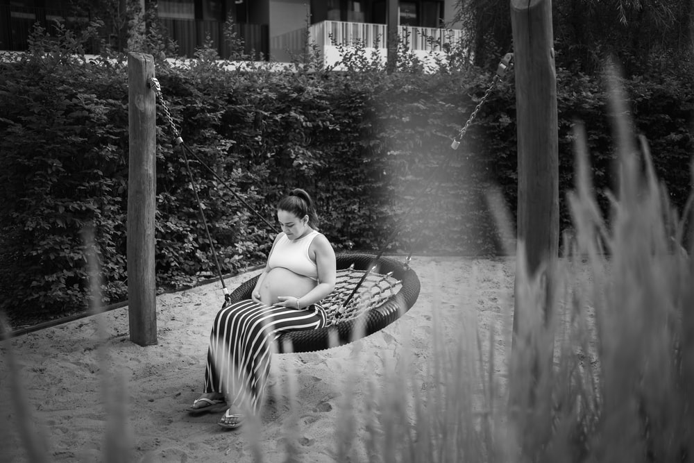 woman in black and white striped dress sitting on chair