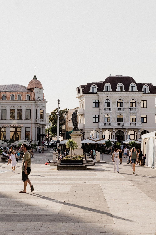 people walking on sidewalk near white concrete building during daytime