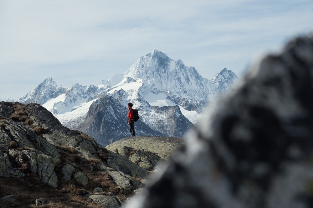 person in red jacket standing on rock mountain during daytime