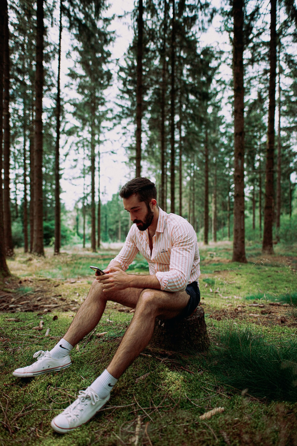 man in white and gray stripe dress shirt sitting on green grass field surrounded by trees