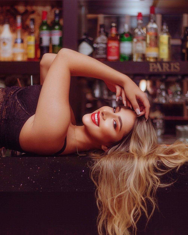 woman in black tank top lying on counter
