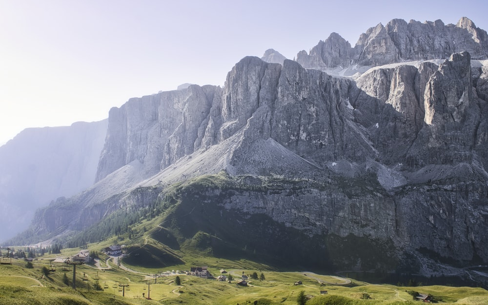 green grass field near gray rocky mountain during daytime