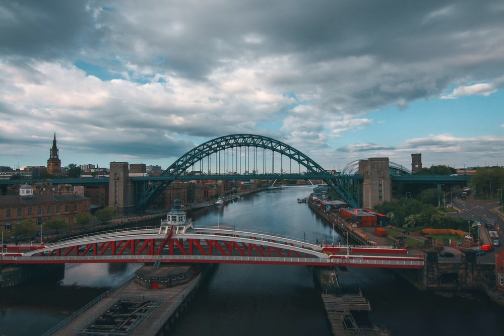 red and white bridge under cloudy sky