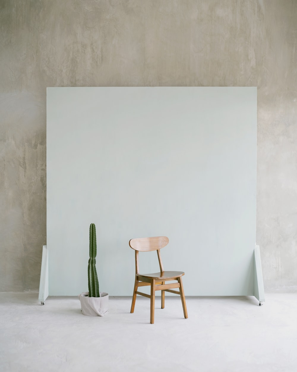 brown wooden seat beside white wall